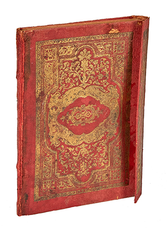an ancient book with a red and gold cover